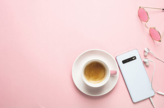 Female office desk. Mobile phone and espresso coffee cup against pink background